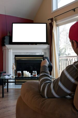 blank screen: Bored man watches a big screen flat panel TV in his living room.  Screen space on the plasma set has empty white copy space ready for your text or image.