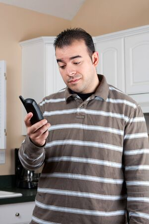 annoying: Young man holding a cordless phone handset in his hand with an annoyed or skeptical expression on his face.