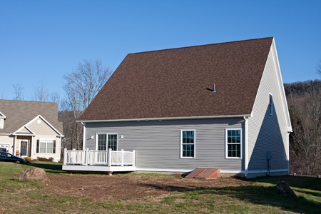 Rear view of a modern custom built house newly constructed with a walk out porch.   photo