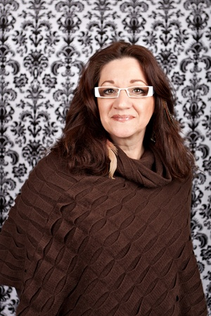 Brunette middle aged woman weather white framed glasses and feather hair extensions and accessories. Archivio Fotografico