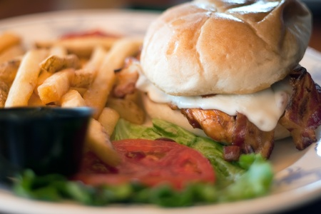 kaiser: Chicken Sandwich on a fresh Kaiser roll with cheese and bacon and a side of french fries. Stock Photo