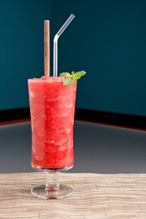 Red fruit flavored frozen cocktail or smoothie beverage with straw and stirring stick. photo