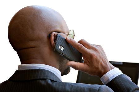 hablando por celular: Un hombre de negocios de unos 30 años hablando por su teléfono inteligente y trabajando en su computadora portátil o netbook. Foto de archivo