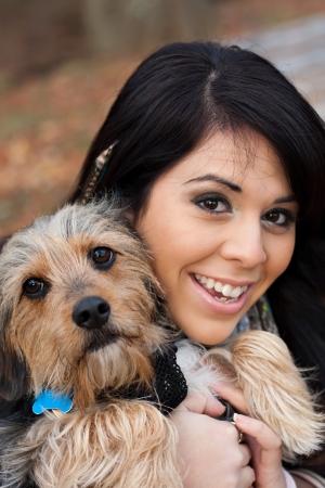 amigos abrazandose: Una joven de unos 20 años por la orilla del mar tiene un lindo beagle de raza mixta perro yorkshire terrier llamado también Borkie.