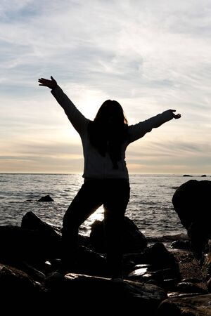 plus sized: Silhouette of a young woman posing on the beach with her arms up in the air.