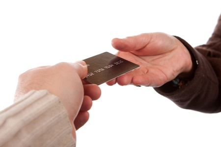 handing: Two hands exchanging a credit debit or gift card isolated over a white background.