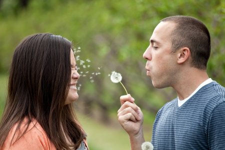 Young happy couple enjoying each others company outdoors.  The man is blowing a dandelion into the face of his girlfriend wife or fiance. photo
