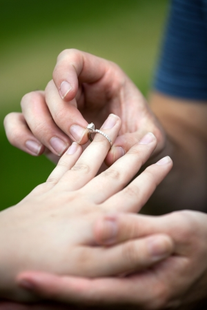 Man placing a diamond engagement ring on the finger of his fiance.  Shallow depth of field with focus on the ring. photo