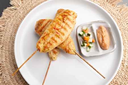 Asian style chicken satay barbecued chicken on skewers with peanut dipping sauce. photo