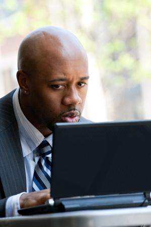 30 代前半の彼の顔に驚きやショック式と屋外彼のラップトップやネットブックのコンピューター上の作業のビジネスの男性。