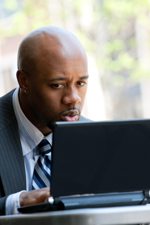 A business man in his early 30s working on his laptop or netbook computer outdoors with a surprised or shocked expression on his face. photo