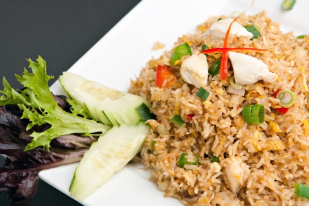 A Thai dish of crab fried rice presented on a square white plate.