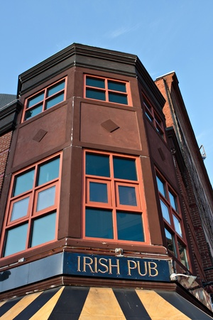 Old building with a sign on front that reads Irish Pub. photo