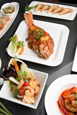 Vers bereide Thaise stijl hele vis red snapper zoete en zure garnalen gyoza dumplings sesam brood en andere pikante Thaise gerechten. Stockfoto - 14192727