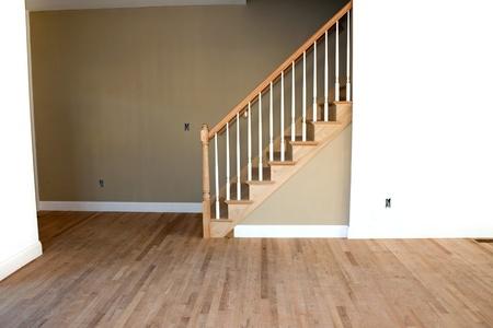 미완성 나무 바닥 계단 및 난간 새로운 주택 건설 객실 인테리어. 전기 및 HVAC 연결이 부분적으로 완료되지 않은 누락 된 콘센트입니다.
