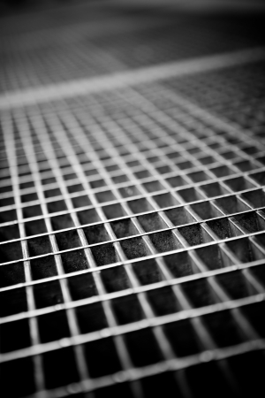 Black and white close up of a sidewalk subway grate with shallow depth of field. Stock Photo