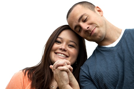 Young happy couple holding hands and showing the diamond engagement ring.  Shallow depth of field with strongest focus on the ring. photo