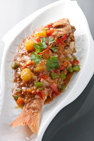 Freshly prepared Thai style whole fish red snapper dinner with tamarind sauce.