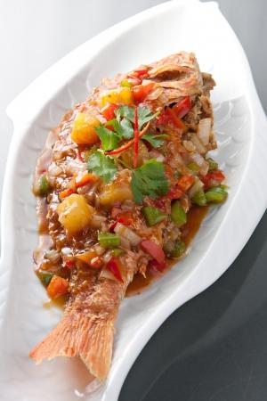 타마 린드 소스와 함께 갓 준비한 태국 스타일 전체 물고기 참돔 저녁 식사.
