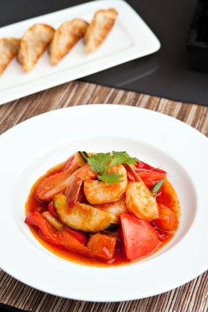 plating: Thai style sweet and sour shrimp dish presented beautifully on a round white plate and pan fried gyoza dumplings.