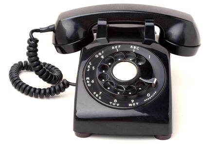 An old black antique rotary style telephone isolated over a white background. photo