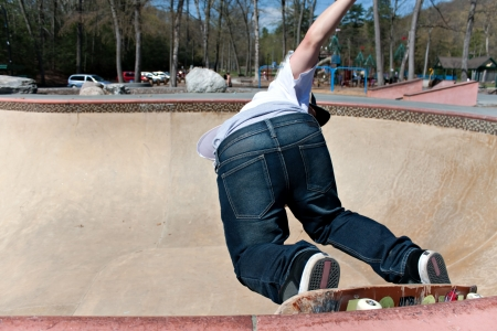 skateboarding tricks: Action shot of a young skateboarder skating sideways against the wall of the bowl at a skate park.