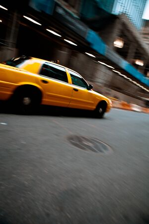 Pnned motion blur of a city street scene with a yellow taxi cab speeding by.  photo