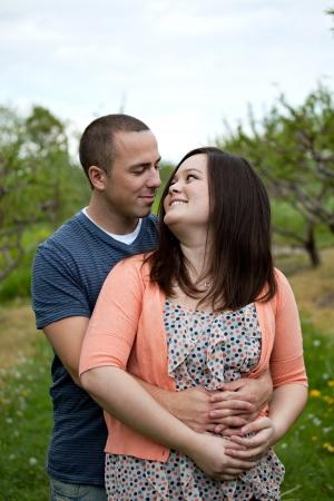 verlobt: Junges Paar glücklich genießen jede andere Firma im Freien zu Fuß durch einen Obstgarten.