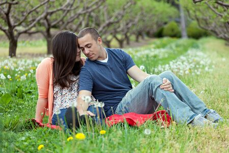 Young happy couple enjoying each others company outdoors on a picnic blanket. photo