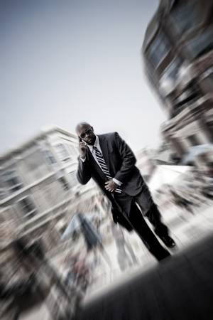 A confident business man walking through the city while talking on his smartphone. Zoom blur vignetting and desaturated toning for added effect. Stock Photo - 14745297