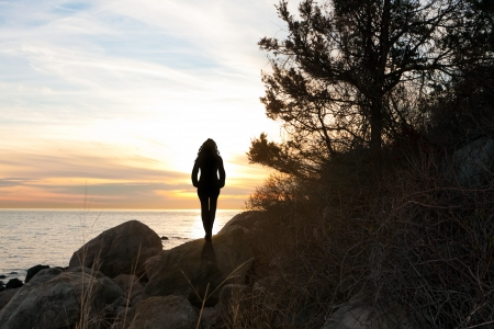 Silhouette of a woman standing in front of the sunset at the New England shoreline.
