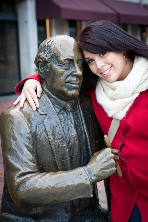 Young woman puts her arm around the public Red Auerbach statue found in Bostons Quincy Market just outside of Faneuil Hall.