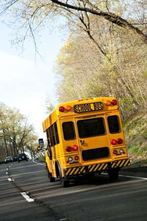 A short yellow school bus driving on the highway. photo