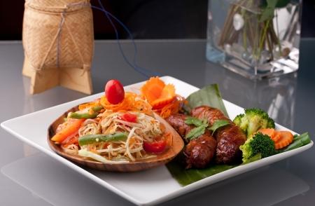 A dish of freshly prepared Thai sausage and som tum green papaya salad.
