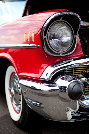 front bumper: A closeup of the headlight and front bumper on a vintage American automobile.