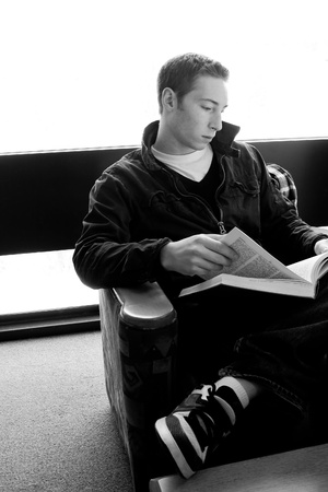 A young college aged man reading a book at the library in black and white. photo