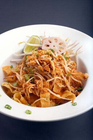 A Thai dish of crispy noodles and bean sprouts in a large white bowl with chop sticks.