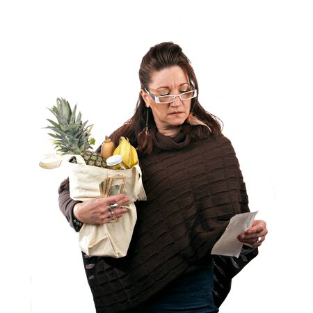 Middle aged woman carefully reviewing her sale receipt and reviewing her grocery shopping bill. Фото со стока