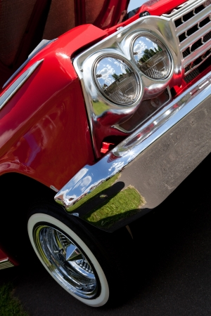 restored: A closeup of the headlights and front bumper on a vintage American automobile. Stock Photo