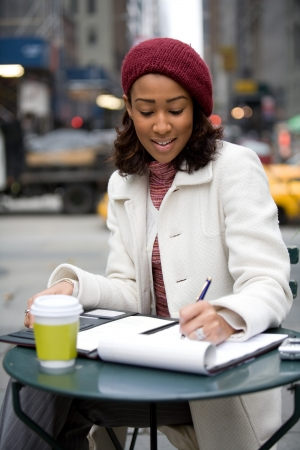 business writing: An African American business woman working in the city outdoors writes something down in her notepad.
