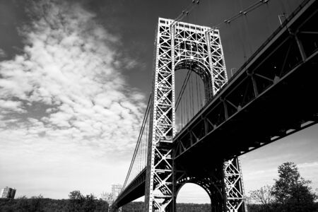 A black and white view of the New York City George Washington Bridge as seen from below. photo