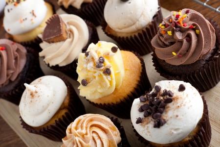Close-up van sommige decadente gastronomische cupcakes frosted met een verscheidenheid van het berijpen smaken.