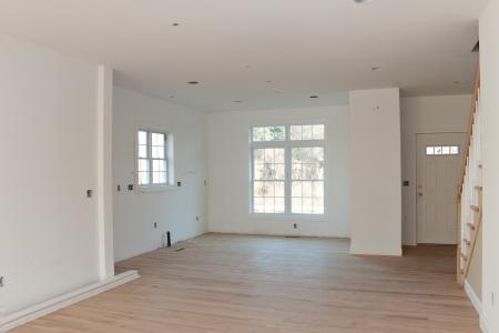 미완성 나무 바닥을 가진 아주 새로운 주택 건설 인테리어 룸. HVAC 전기 콘센트와 조명기구는 부분적으로 미완성이다.