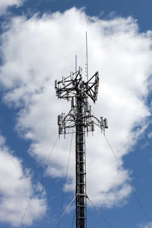 3g: A cellular antenna tower isolated over a blue sky with white fluffy clouds. Stock Photo