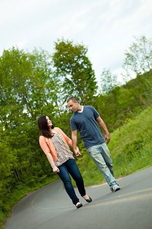 Young happy couple enjoying each others company outdoors walking down an empty road. A very fitting theme for the start of marriage or any romantic relationship. photo