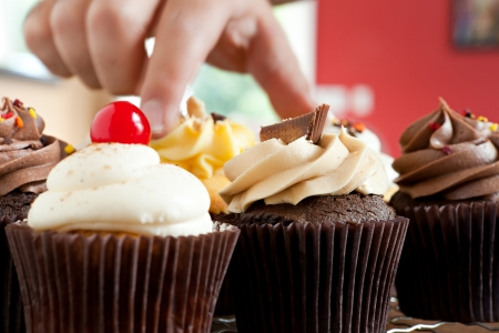 grabbing hand: Close up of some decadent gourmet cupcakes frosted with a variety of frosting flavors.
