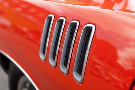 vents: Close up detail of the louvered fender vents on a late model American muscle car with chrome accents.