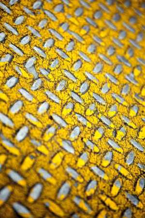 diamondplate: Close up of real diamond plate material.  Most of the yellow paint is chipped and scratched off. Shallow depth of field.