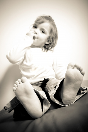 two year old: Close up of a barefoot toddler aged little girl in sepia tone. Shallow depth of field with sharpest focus on the feet and toes. Stock Photo