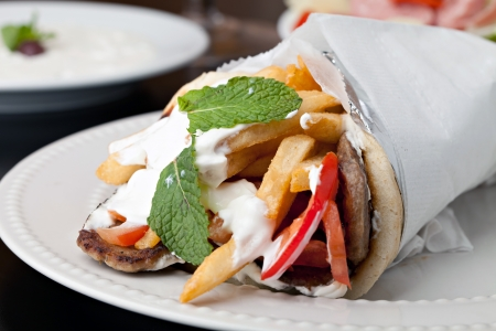 Traditional Gyro sandwich with meat  tzatziki sauce tomato onions and fried potato garnished with mint. Shallow depth of field. Standard-Bild